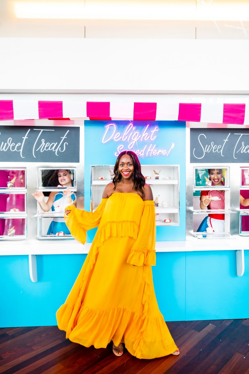 Amur Odessa Maxi | The Influencers of Color You Need to Follow by popular DC lifestyle blogger, Alicia Tenise: image of woman wearing a yellow Amur Odessa Maxi in front of retro dessert shop.