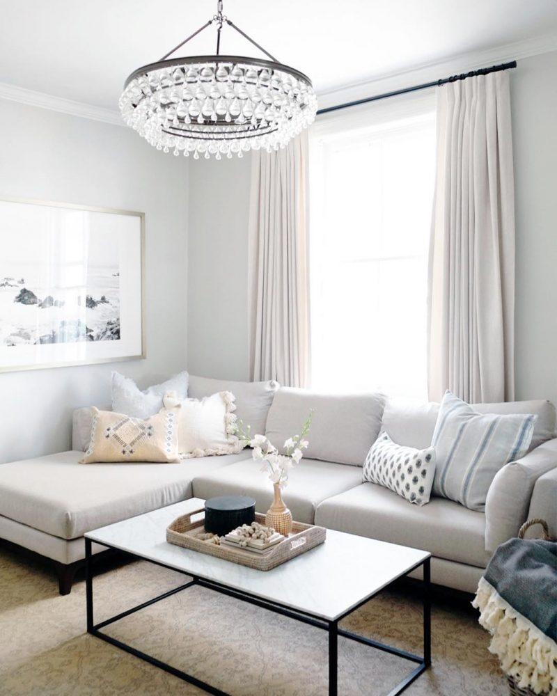 New Home Decor Ideas by popular Washington D.C. life and style blogger, Alicia Tenise: image of a light grey sectional couch, modern crystal chandelier, and marble and iron coffee table.