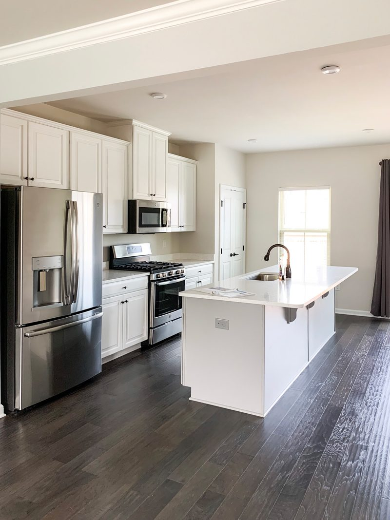 New Home Decor Ideas by popular Washington D.C. life and style blogger, Alicia Tenise: image of a modern styled kitchen with faux wood flooring, stainless steel appliances and white cabinetry.