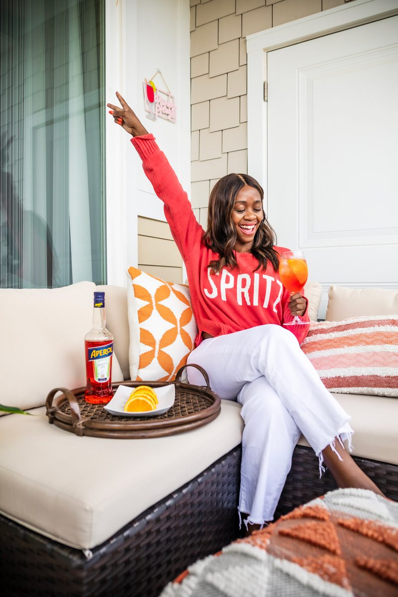7 for All Mankind Alexa High Waist Crop Wide Leg Jeans, Patio Decor Ideas | The Perfect End of Summer Cocktail: The Aperol Spritz by popular Washington D.C. life and style blogger, Alicia Tenise: image of a woman sitting outside wearing a show me your mumu arroyo sweater and drinking an Aperol Spritz cocktail.