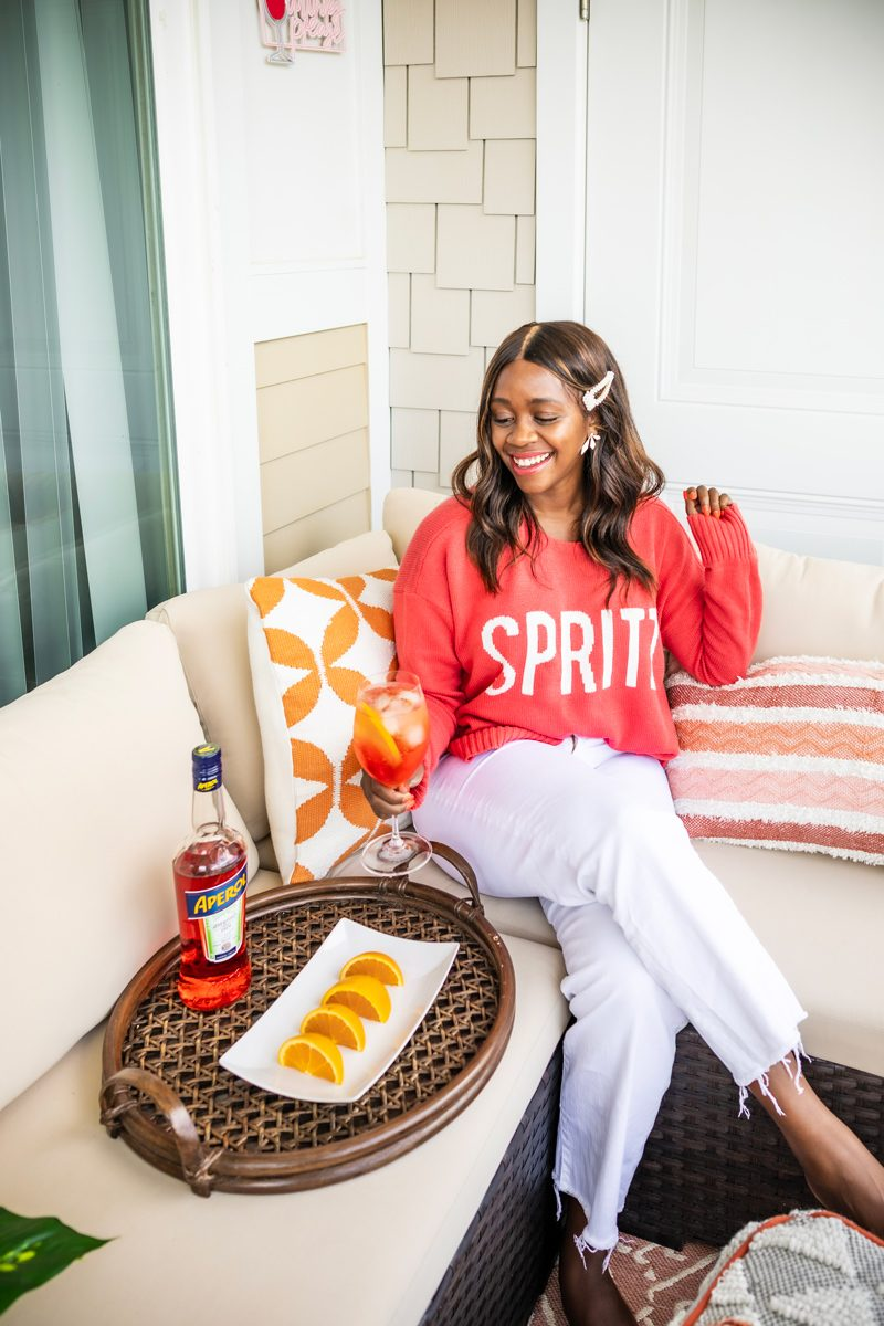 show me your mumu arroyo sweater - spritz graphic | The Perfect End of Summer Cocktail: The Aperol Spritz by popular Washington D.C. life and style blogger, Alicia Tenise: image of a woman sitting outside wearing a show me your mumu arroyo sweater and drinking an Aperol Spritz cocktail.