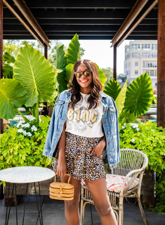 Cute Leopard Fashion Pieces featured by top US fashion blogger, Alicia Tenise: image of a woman wearing a Madewell oversized denim jacket, Anine Bing graphic tee, South Moon Under leopard shorts, and a Cult Gaia max bag.