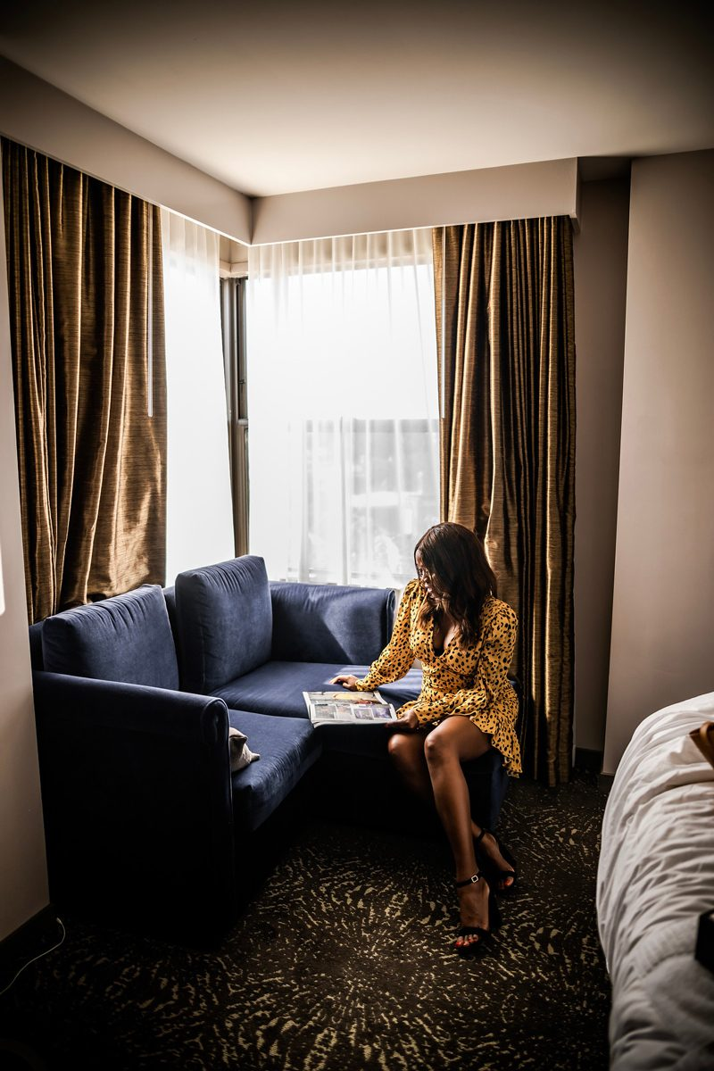A Day in the Life of an Influencer by popular Washington D.C. influencer, Alicia Tenise: image of a woman sitting on a hotel room couch and reading a magazine.