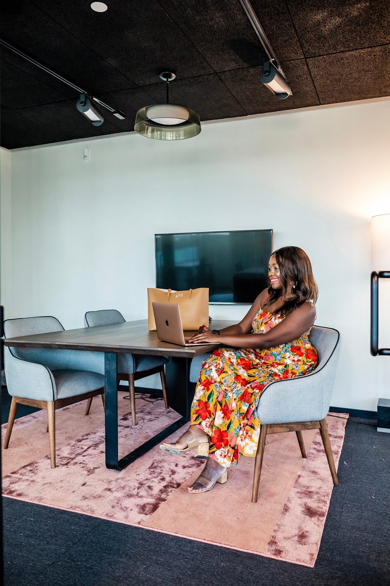 My Office Tour at Industrious Alexandria, VA by popular DC blogger, Alicia Tenise: image of a woman wearing a floral dress and sitting in a gray armchair at a table and working on her laptop.