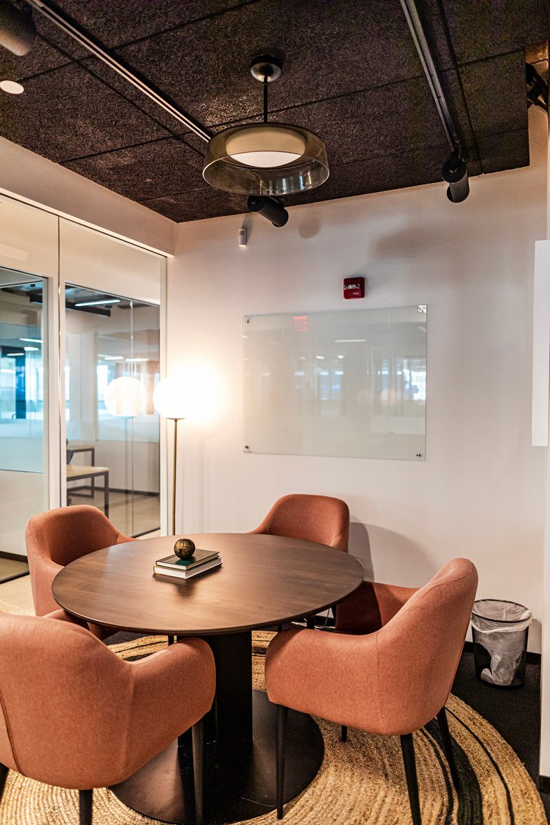 My Office Tour at Industrious Alexandria, VA by popular DC blogger, Alicia Tenise: image of a round conference table with pink fabric armchairs.