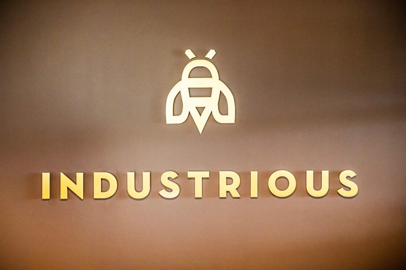 My Office Tour at Industrious Alexandria, VA by popular DC blogger, Alicia Tenise: image of Industrious logo on a brown wall.