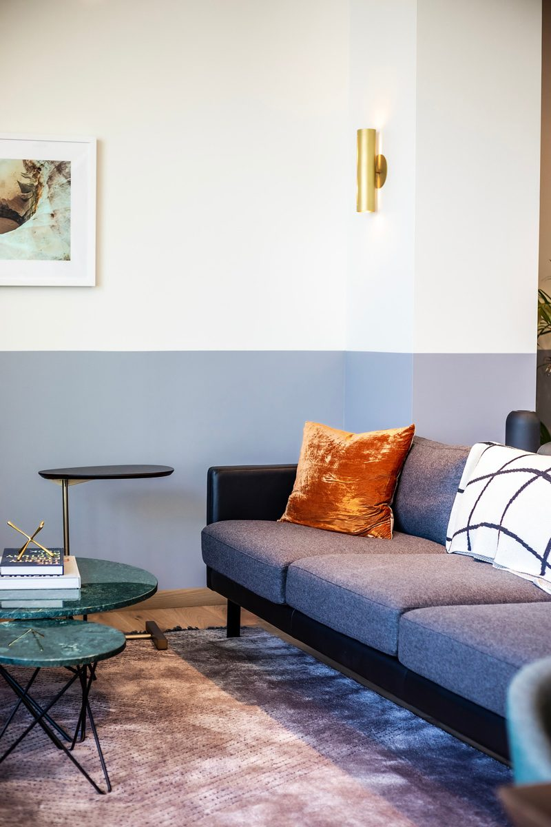 My Office Tour at Industrious Alexandria, VA by popular DC blogger, Alicia Tenise: image of a blue mid-century modern couch, purple rug, orange velvet pillows and green marble coffee tables.