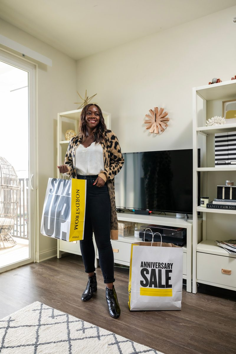 Nordstrom Anniversary Sale: Top Beauty Picks featured by top Washington D.C. fashion blog, Alicia Tenise: image of a woman standing in her living room and holding a Nordstrom Anniversary shopping bag.