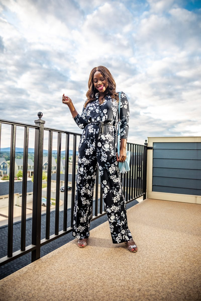 Black Floral Jumpsuit from Walmart | Summer to Fall Looks: Two Transitional Outfit Ideas Under $100 by popular Washington D.C. fashion blogger, Alicia Tenise: image of a woman standing outside and wearing a Walmart Calvin Klein  Three-Quarter Floral Tie Waist Jumpsuit and Metallic Sky Circle Crossbody.