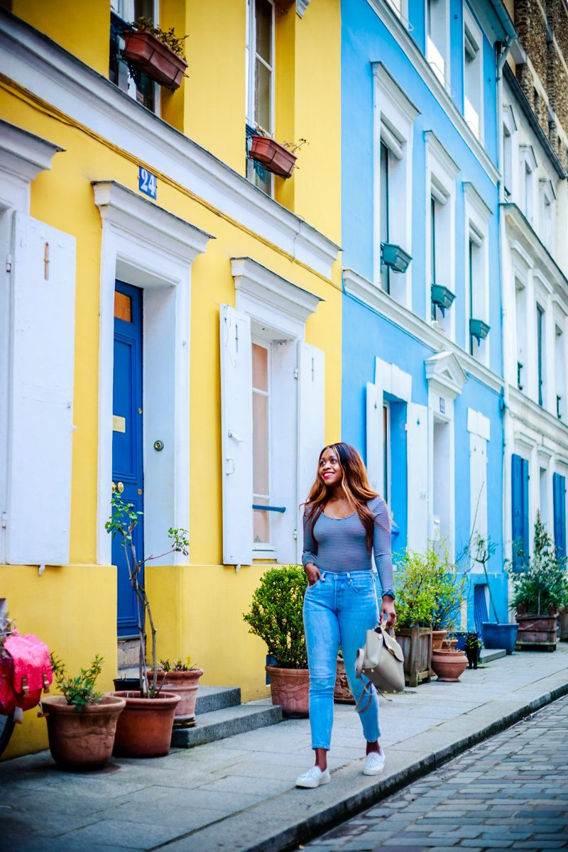 Why I Didn't Travel That Much This Summer + My Fall Travel Bucket List Plans by popular Washington D.C. travel blogger, Alicia Tenise: image of a woman walking down a street with colorful yellow and blue buildings.