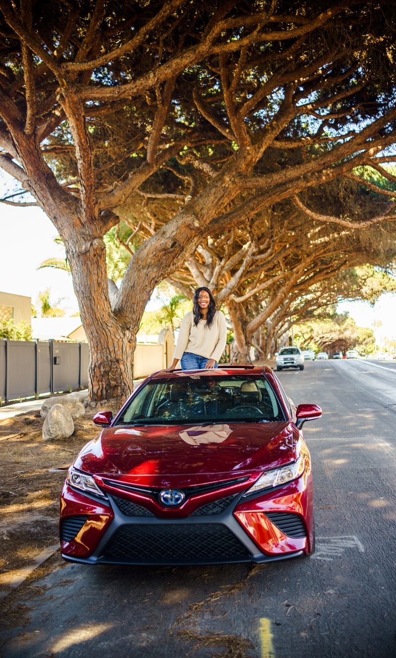 Why I Didn't Travel That Much This Summer + My Fall Travel Bucket List Plans by popular Washington D.C. travel blogger, Alicia Tenise: image of a woman sitting on top of her car under some trees.