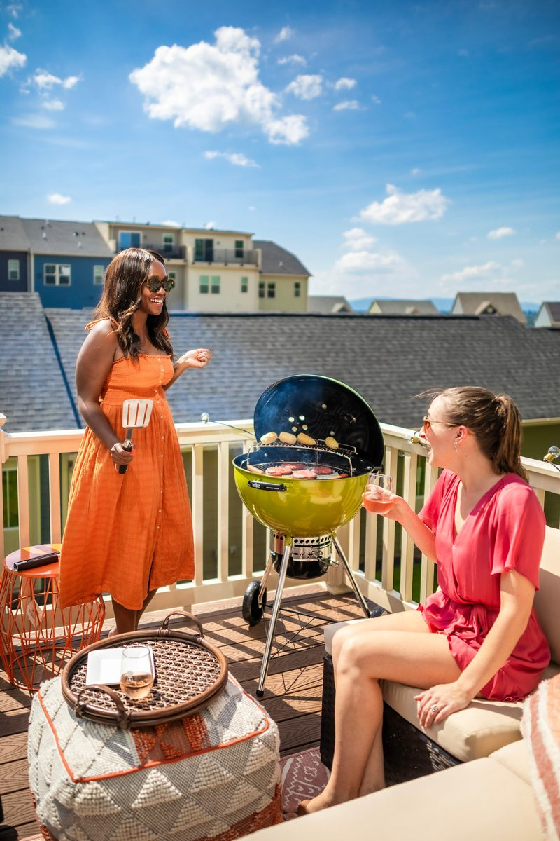 5 Things No One Tells You About Moving to the Suburbs by popular Washington D.C. lifestyle blogger, Alicia Tenise:image of two women sitting outside on a patio and grilling up some hamburgers.