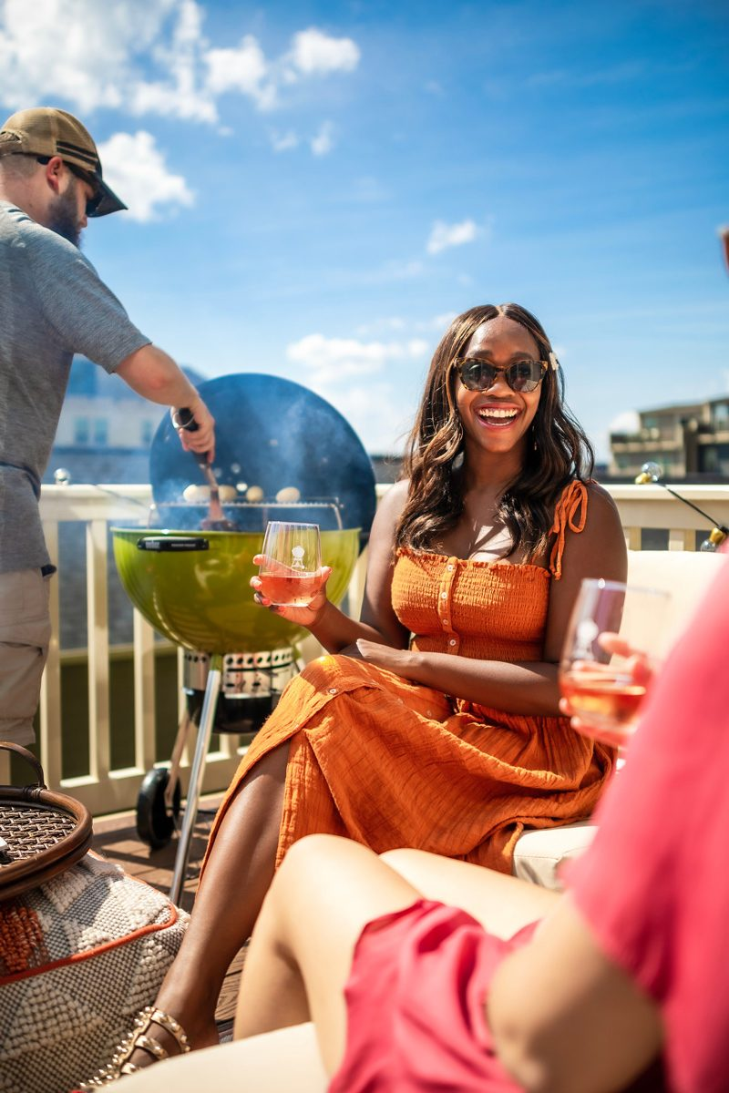 5 Things No One Tells You About Moving to the Suburbs by popular Washington D.C. lifestyle blogger, Alicia Tenise: image of a man and two women on a patio drinking cocktails and grilling burgers.