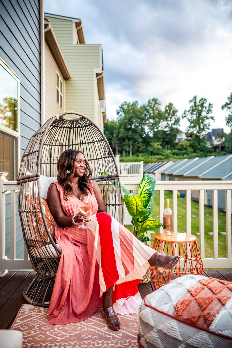 Tome Pleated Printed Dress | The Most Popular Blog Posts of 2019 by popular Washington DC life and style blogger, Alicia Tenise: image of a woman holding a glass of wine and sitting on her back porch.