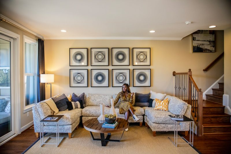 Brambleton VA: The Tech-Savvy Town That Needs to Be On Your Radar by popular life and style blogger, Alicia Tenise: image of a woman sitting in the living room of a townhouse.