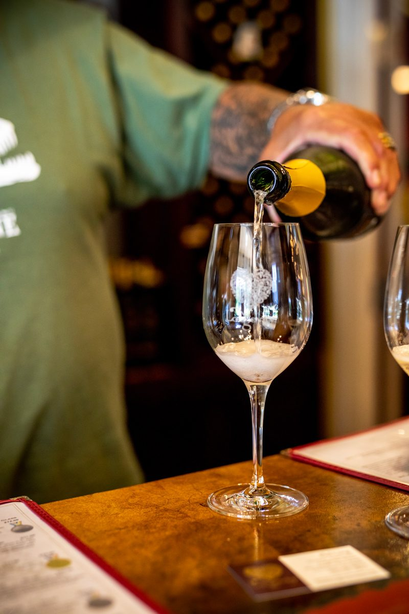 Longevity Wines in Livermore Valley CA | Black Owned Wineries by popular D.C. lifestyle blogger, Alicia Tenise: image of a man pouring a glass of white wine into a clear wine glass.