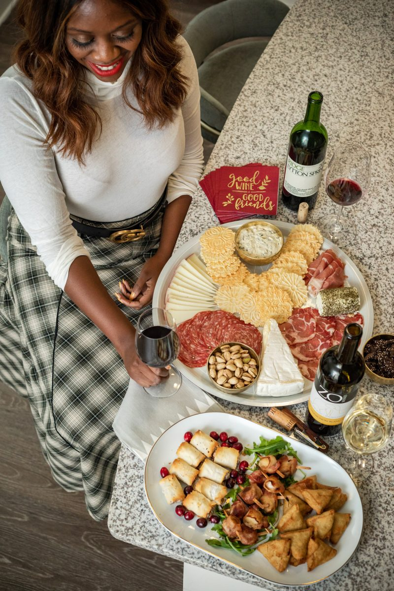 The Best Wines for the Holidays | The Best Wines for Thanksgiving Dinner by popular Washington D.C. lifestyle blogger, Alicia Tenise: image of a woman sitting next to a charcuterie board and holding a glass of red wine.
