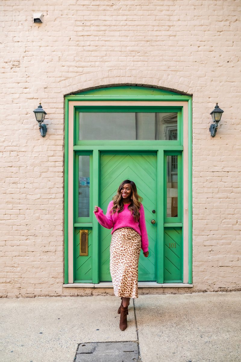 Abercrombie Slouchy Crew Sweater, Free People Normani Bias Printed Skirt | Colorful Sweaters to Liven Up Your Wardrobe This Winter by popular Washington D.C. fashion blogger, Alicia Tenise: image of a woman standing in front of a white brick building with a green door and wearing a pink Abercrombie slouch sweater, Free People Normani Bias Printed Skirt, and Kendra Scott Kase Rose Gold Fringe Earrings In Rose Gold Filigree.
