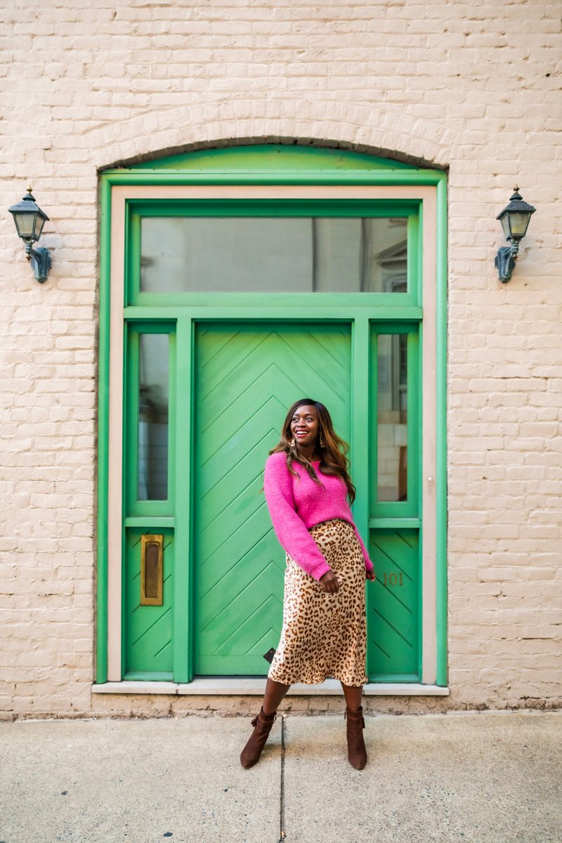 How to Style a Silk Skirt, Free People Cheetah Midi Skirt | Silk Skirt by popular D.C. fashion blogger, Alicia Tenise: image of Alicia Tenise standing in front of a white brick building with a green wooden door and wearing a pink sweater with a Free People Cheetah print silk skirt and brown suede ankle boots.
