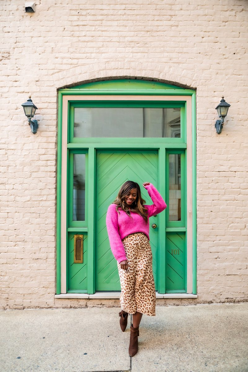 Silk Skirt by popular D.C. fashion blogger, Alicia Tenise: image of Alicia Tenise standing in front of a white brick building with a green wooden door and wearing a pink sweater with a Free People Cheetah print silk skirt and brown suede ankle boots.