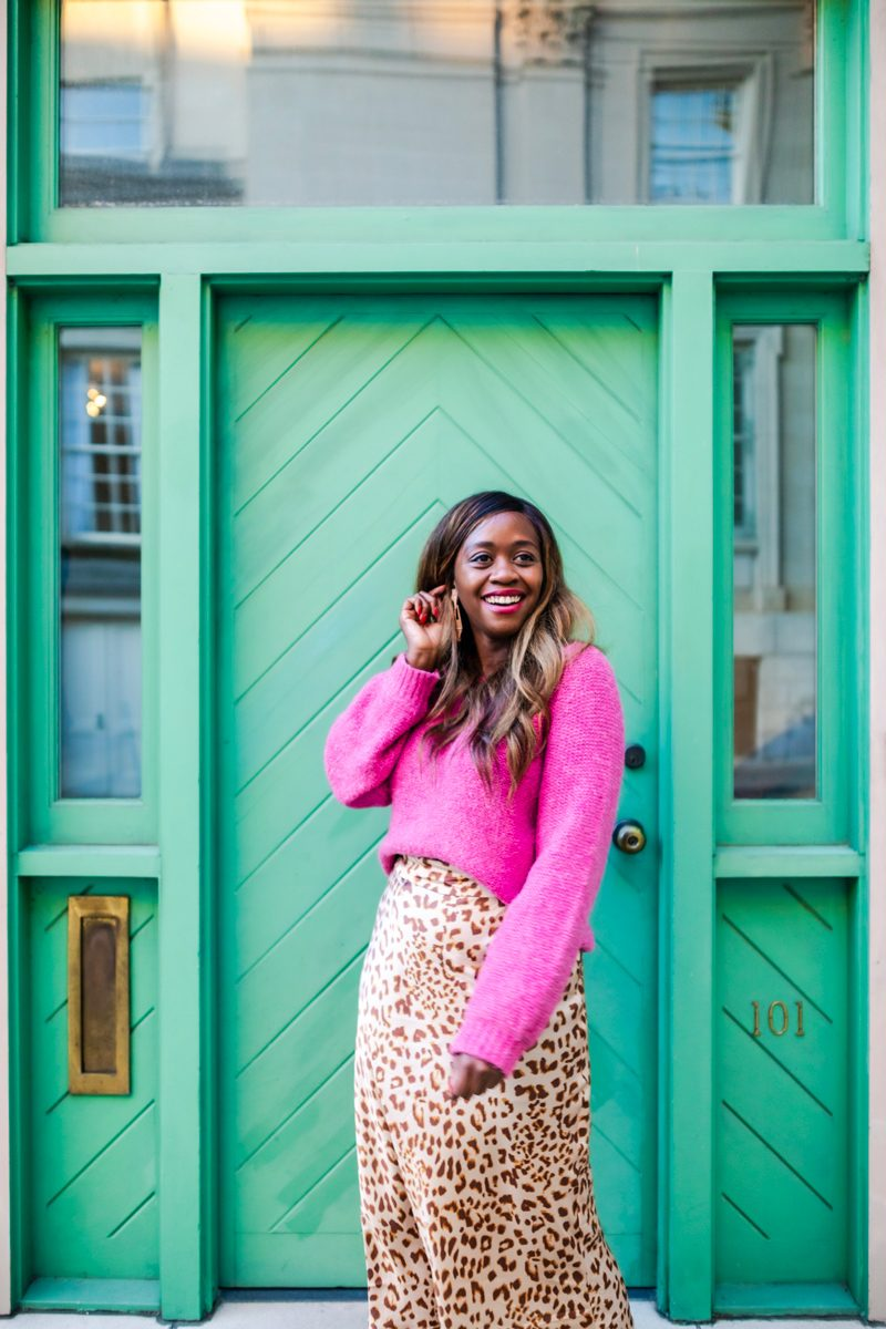 Bold Sweaters for Winter | Colorful Sweaters to Liven Up Your Wardrobe This Winter by popular Washington D.C. fashion blogger, Alicia Tenise: image of a woman standing in front of a white brick building with a green door and wearing a pink Abercrombie slouch sweater, Free People Normani Bias Printed Skirt, and Kendra Scott Kase Rose Gold Fringe Earrings In Rose Gold Filigree.