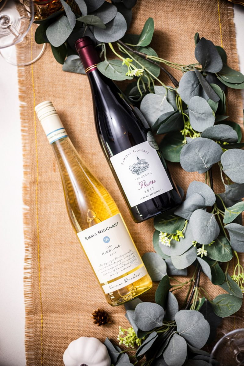 The Best Wines for Thanksgiving Dinner by popular Washington D.C. lifestyle blogger, Alicia Tenise: image of a burlap runner, eucalyptus leaves and a red and white bottle of wine.