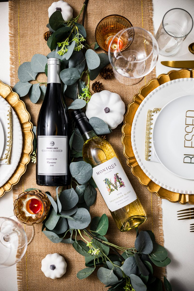 The Best Wines for Thanksgiving Dinner by popular Washington D.C. lifestyle blogger, Alicia Tenise: image of a table set with gold utensils, wine glasses, gold plate chargers, white ceramic plates, burlap runner, eucalyptus leaves and bottles of wine.