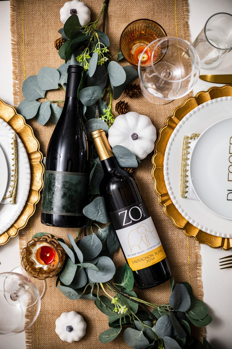The Best Wines for Thanksgiving Dinner by popular Washington D.C. lifestyle blogger, Alicia Tenise |The Best Wines for Thanksgiving Dinner by popular Washington D.C. lifestyle blogger, Alicia Tenise: image of a table set with gold utensils, wine glasses, gold plate chargers, white ceramic plates, burlap runner, eucalyptus leaves and bottles of wine.
