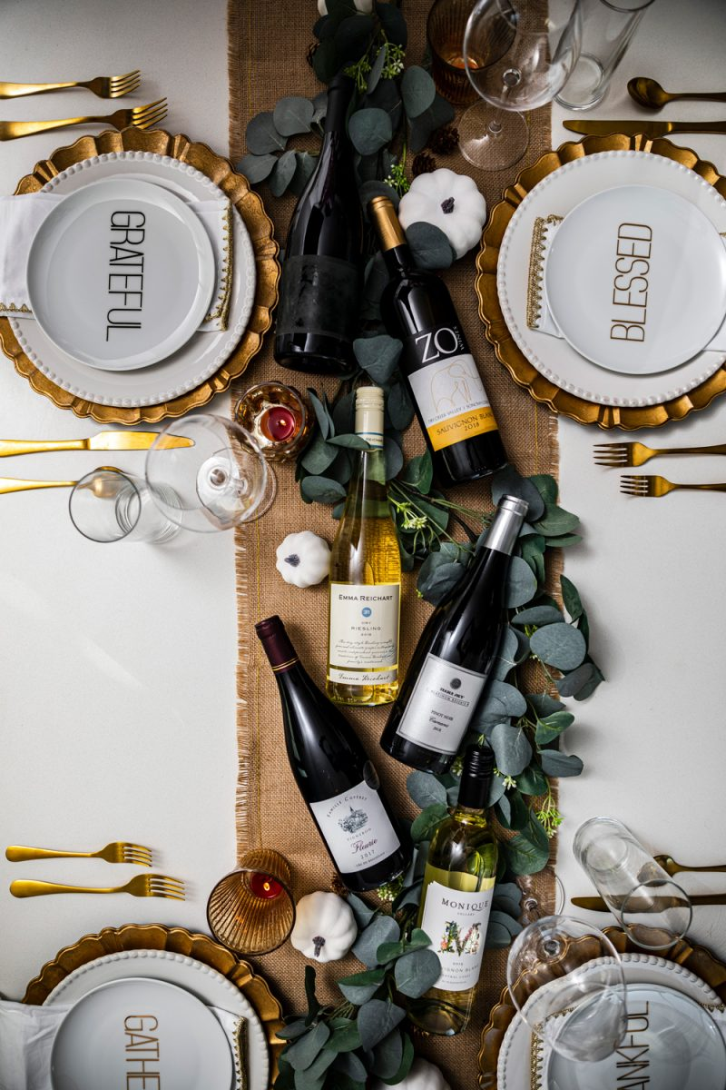 The Best Wines for the Holidays | The Best Wines for Thanksgiving Dinner by popular Washington D.C. lifestyle blogger, Alicia Tenise: image of a table set with gold utensils, wine glasses, gold plate chargers, white ceramic plates, burlap runner, eucalyptus leaves and bottles of wine.