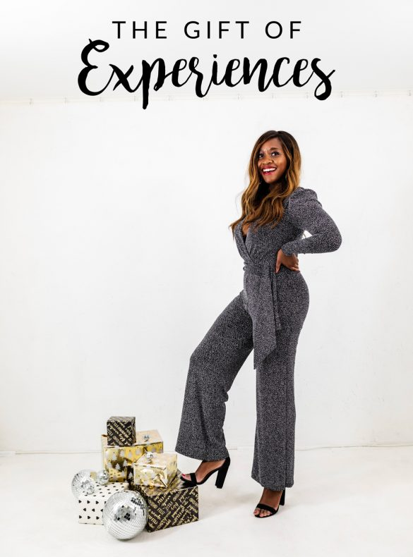 Gift Guide: Experience Gift Ideas by popular life and style blogger, Alicia Tenise: image of a woman wearing a a jumpsuit and standing next to a pile of gifts.