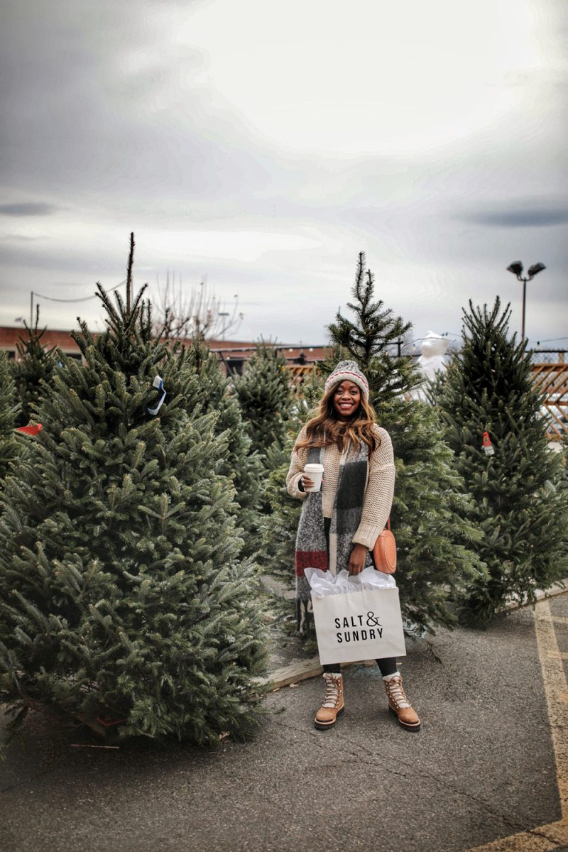 Best Small Businesses to Shop during the Holidays | Free People My Only Sunshine Sweater, Roots Cabin Collection | Top Women Owned Small Businesses to Support This Holiday Season by popular Washington D.C. life and style blogger, Alicia Tenise: image of woman standing by some Christmas trees and holding a Salt & Sundry shopping bag.