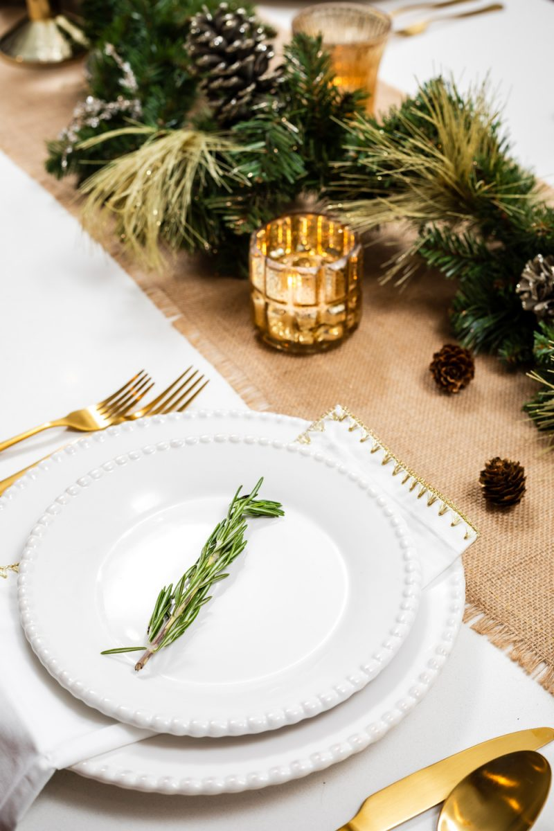Budget-Friendly Christmas Table Decorations | Holiday Tablescape: My Christmas Table Decor by popular Washington D.C. life and style blogger, Alicia Tenise: image of a woman holding a tray with two wine glasses on it and standing next to a West Elm Canto Dining Table with Joss and Main Camron Velvet Upholstered Side Chairs and decorated with Pier 1 Keely Stoneware White Dinnerware, Amazon Sharecook Matte Black Silverware Set, Pier 1 Gilded Faux Pine Garland, Pier 1 Unscented Gold Taper Candles, and Pier 1 White Napkin with Gold Trim.