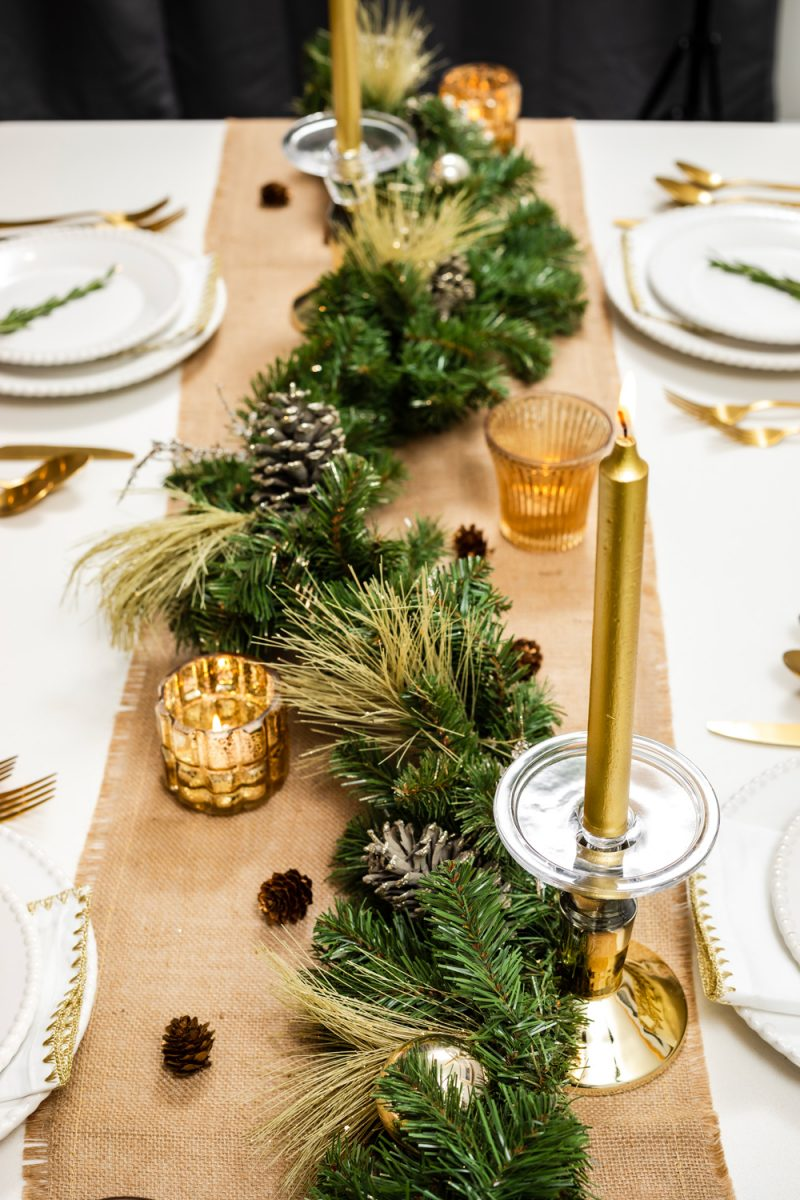 Christmas Table Decorations | Holiday Tablescape: My Christmas Table Decor by popular Washington D.C. life and style blogger, Alicia Tenise: image of a woman holding a tray with two wine glasses on it and standing next to a West Elm Canto Dining Table with Joss and Main Camron Velvet Upholstered Side Chairs and decorated with Pier 1 Keely Stoneware White Dinnerware, Amazon Sharecook Matte Black Silverware Set, Pier 1 Gilded Faux Pine Garland, Pier 1 Unscented Gold Taper Candles, and Pier 1 White Napkin with Gold Trim.