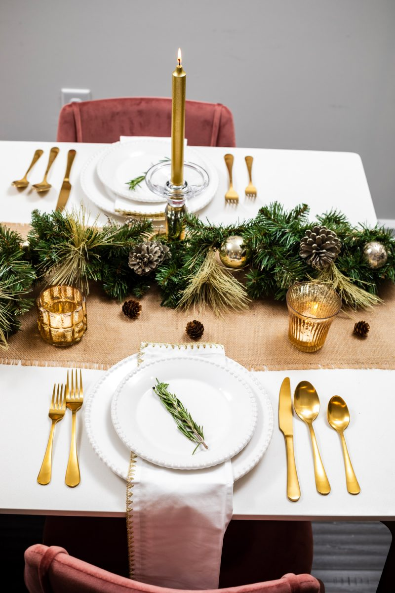 Holiday Tablescape Idea | Holiday Tablescape: My Christmas Table Decor by popular Washington D.C. life and style blogger, Alicia Tenise: image of a woman holding a tray with two wine glasses on it and standing next to a West Elm Canto Dining Table with Joss and Main Camron Velvet Upholstered Side Chairs and decorated with Pier 1 Keely Stoneware White Dinnerware, Amazon Sharecook Matte Black Silverware Set, Pier 1 Gilded Faux Pine Garland, Pier 1 Unscented Gold Taper Candles, and Pier 1 White Napkin with Gold Trim.