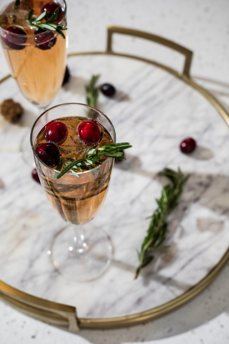 Holiday Cocktail Idea | A Christmas Mimosa That Will Dazzle Your Guests by popular Washington D.C. life and style blogger, Alicia Tenise: image of filled wine glasses on a marble serving tray.