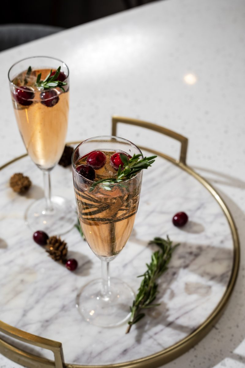 Christmas Mimosa | A Christmas Mimosa That Will Dazzle Your Guests by popular Washington D.C. life and style blogger, Alicia Tenise: image of filled wine glasses on a marble serving tray.