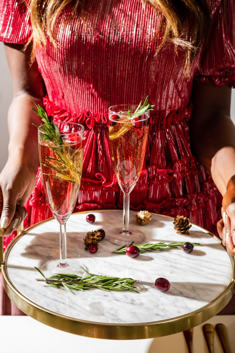 Christmas Mimosas | A Christmas Mimosa That Will Dazzle Your Guests by popular Washington D.C. life and style blogger, Alicia Tenise: image of a woman wearing a Nordstrom Halogen x Atlantic-Pacific Ruffle Plissé Dress and holding a serving tray with beverages on it.
