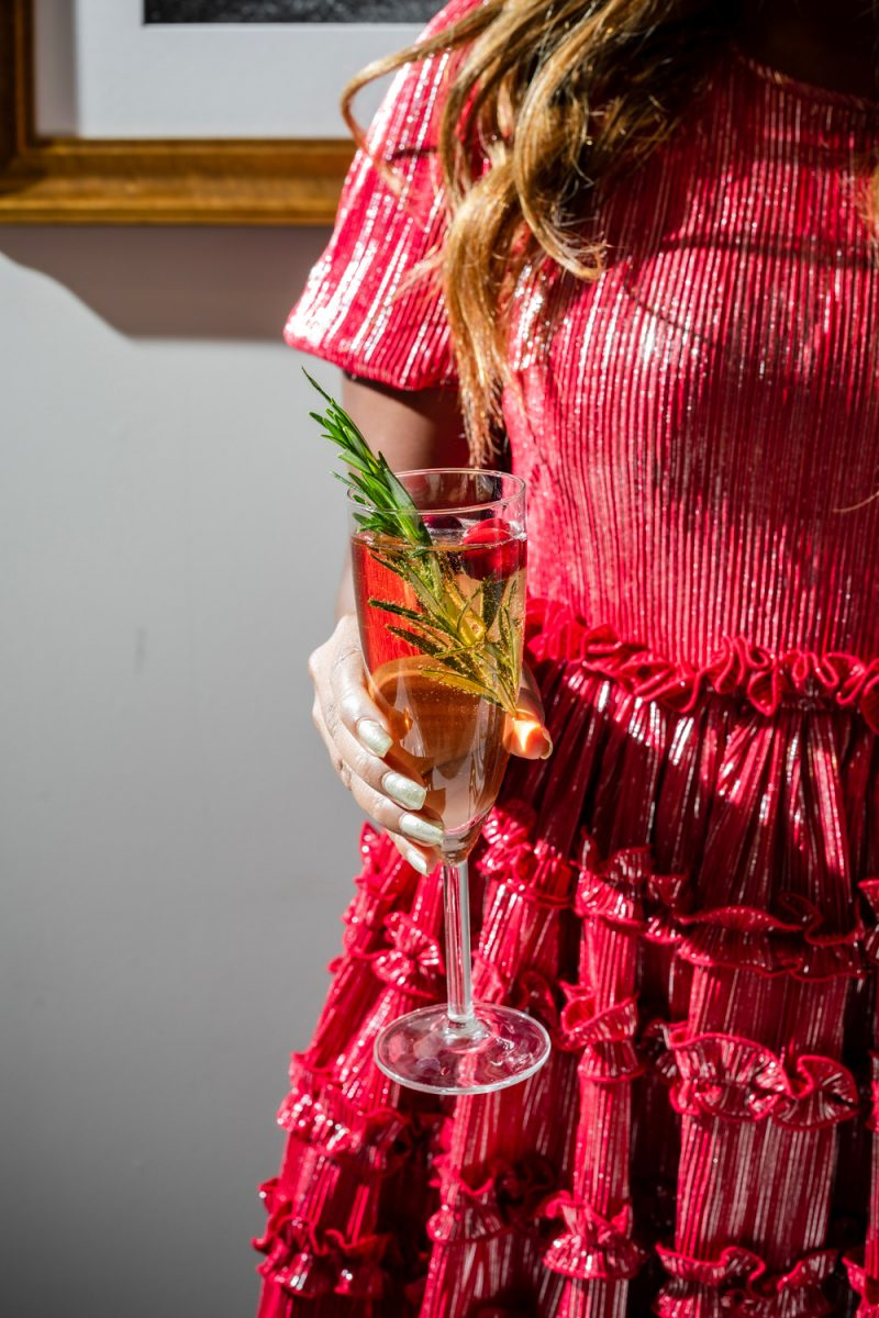 Christmas Mimosa Recipe | A Christmas Mimosa That Will Dazzle Your Guests by popular Washington D.C. life and style blogger, Alicia Tenise: image of a woman wearing a Nordstrom Halogen dress and holding a wine glass.