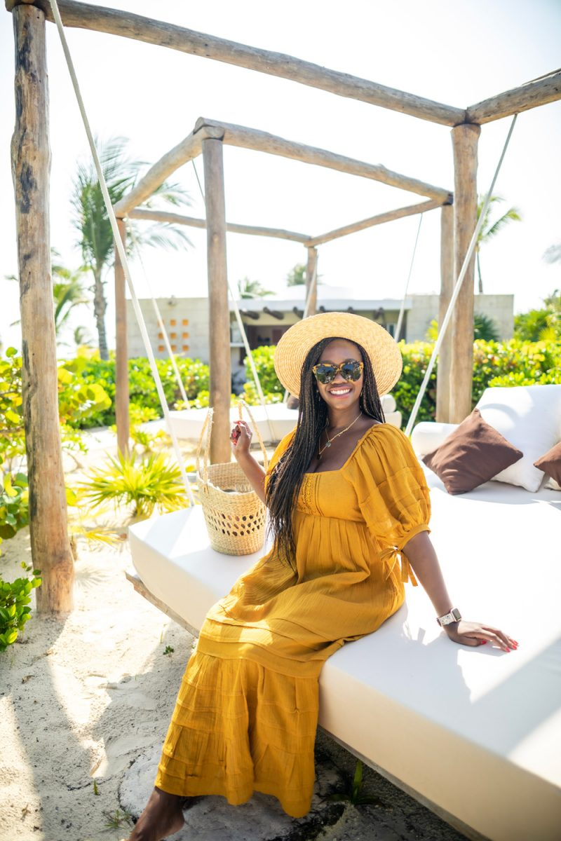 Cancun Packing List by popular international travel blogger, Alicia Tenise: image of a woman wearing a Free People Lets Be Friends Midi Dress, Nordstrom Joanna Straw Hat BRIXTON, Revolve Number One Karen Walker brand: Karen Walker, and ShopBop Gorjana Faye Layer Set Necklace.