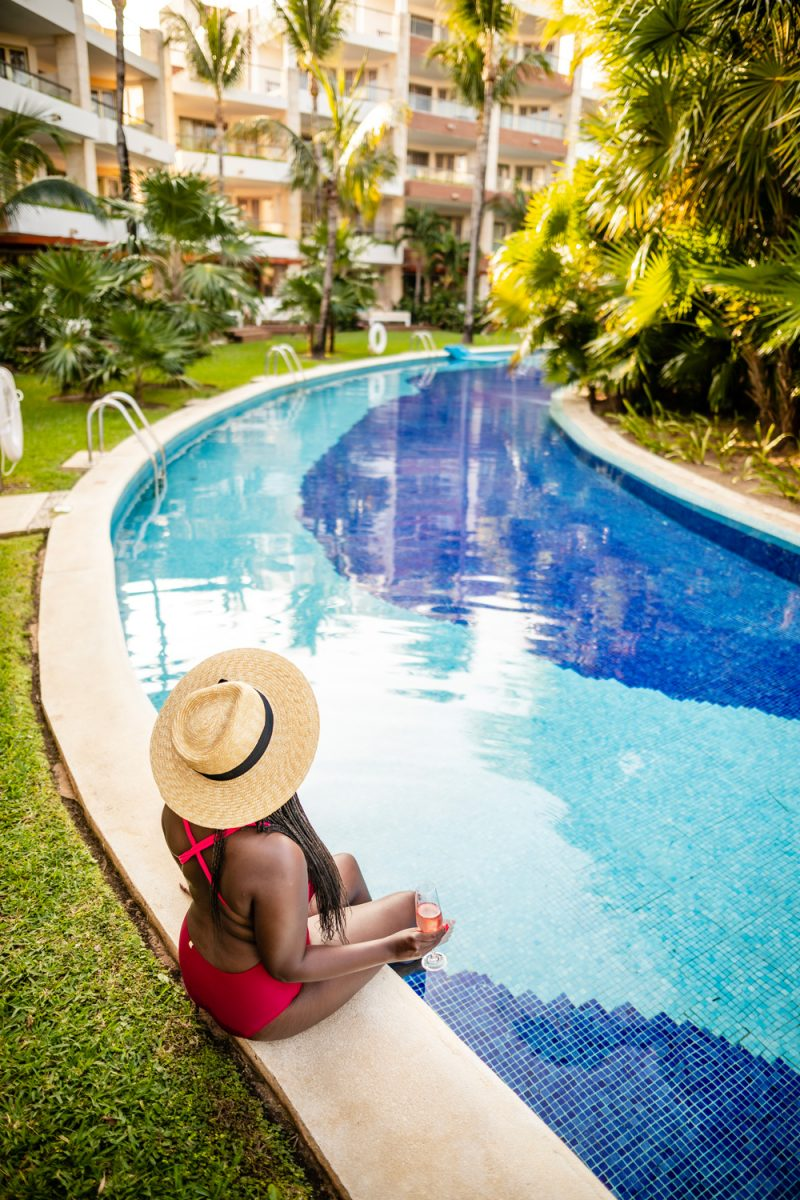 Cancun Packing List by popular international travel blogger, Alicia Tenise: image of a woman sitting by a lazy river and wearing a red swim suit and straw fedora.