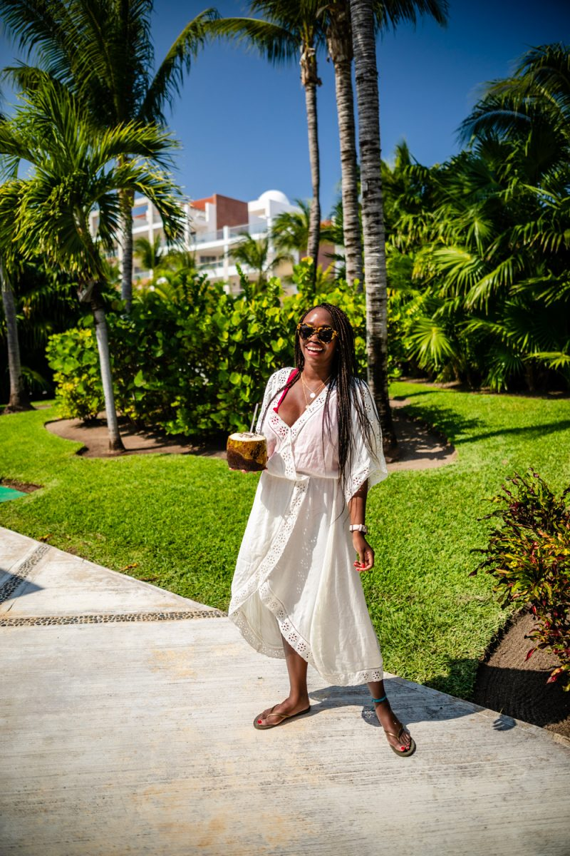 Cancun Packing List by popular international travel blogger, Alicia Tenise: image of a woman wearing a white cover up and Revolve Number One Karen Walker brand: Karen Walker.