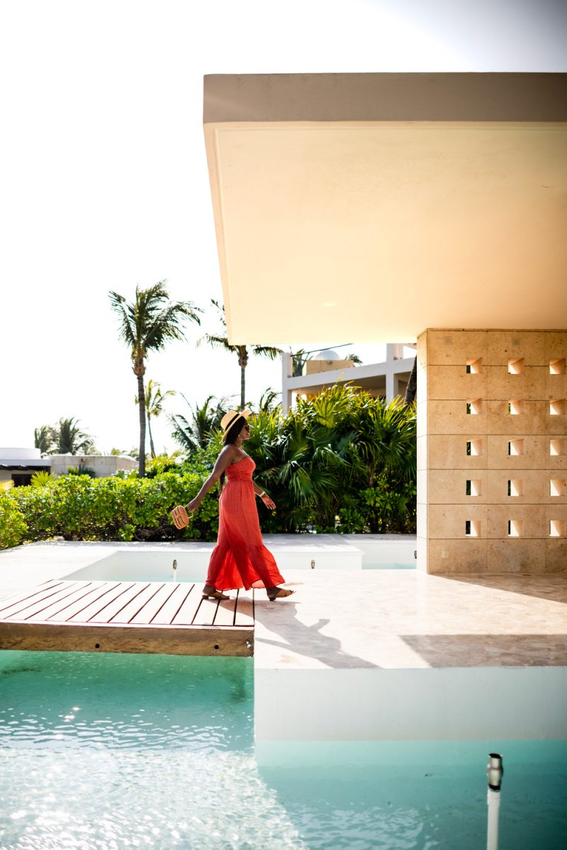 Excellence Playa Mujeres | How to Deal with Stress and Anxiety by popular DC lifestyle blogger, Alicia Tenise: image of a woman walking outside and wearing a ShopBop Free People Free People Little Of Your Love Jumpsuit, Nordstrom Brixton Joanna Straw Hat, ShopBop Karen Walker The Number One Sunglasses, and holding a Moda Operandi Cult Gaia bag.