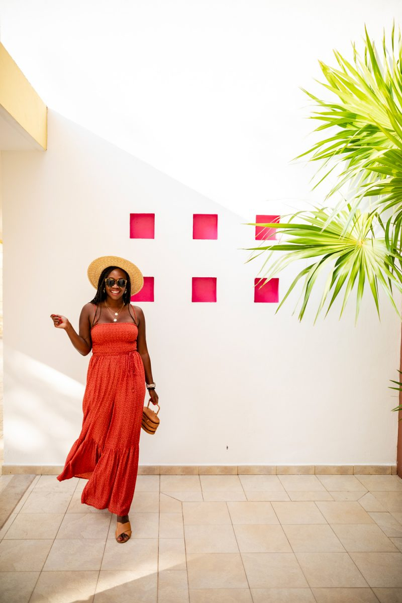 Cancun Packing List by popular international travel blogger, Alicia Tenise: image of a woman wearing Revolve Number One Karen Walker brand: Karen Walker sunglasses, ShopBop Free People Little Of Your Love Jumpsuit, and Nordstrom Joanna Straw Hat BRIXTON.
