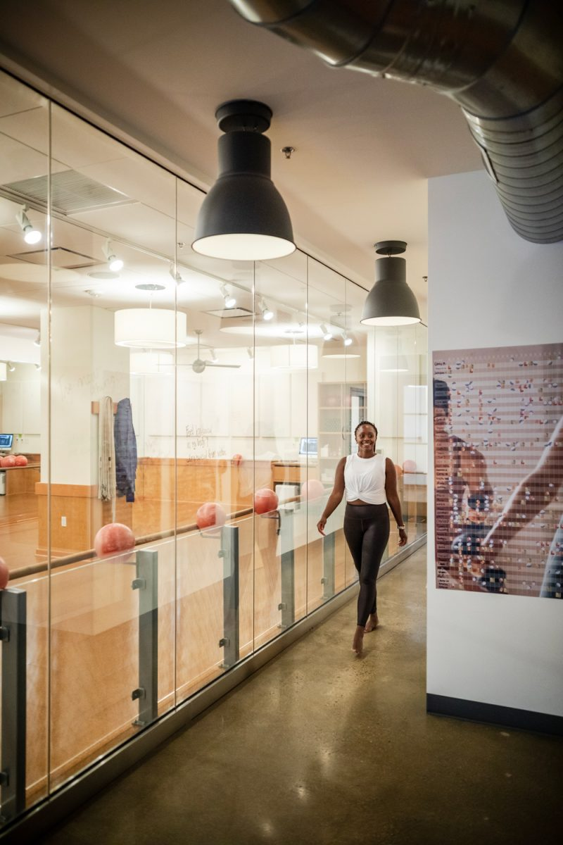 Best Workout Classes in DC   Best Workout Classes in DC by popular DC lifestyle blogger, Alicia Tenise: image of a woman walking through a hallway at Orange Theory.
