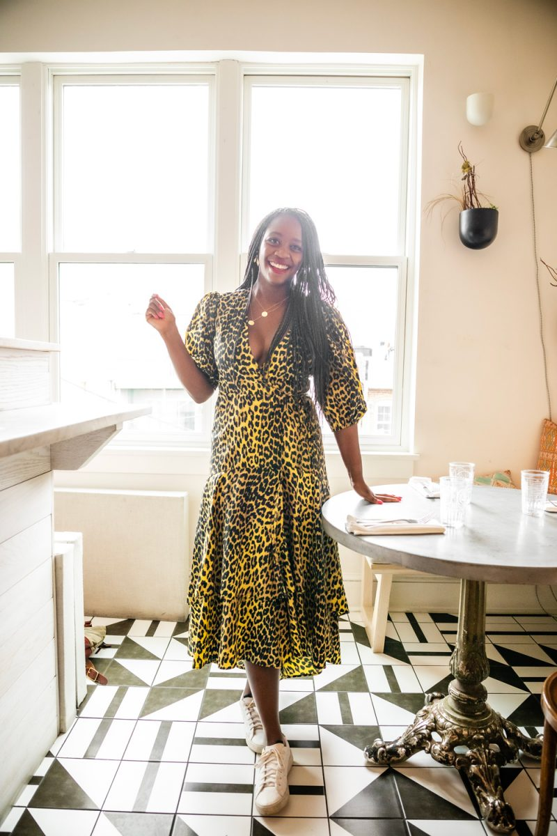 Blogging in 2020 by popular DC blogger, Alicia Tenise: image of a woman standing next to a table in a cafe and wearing a yellow leopard print dress with white sneakers.