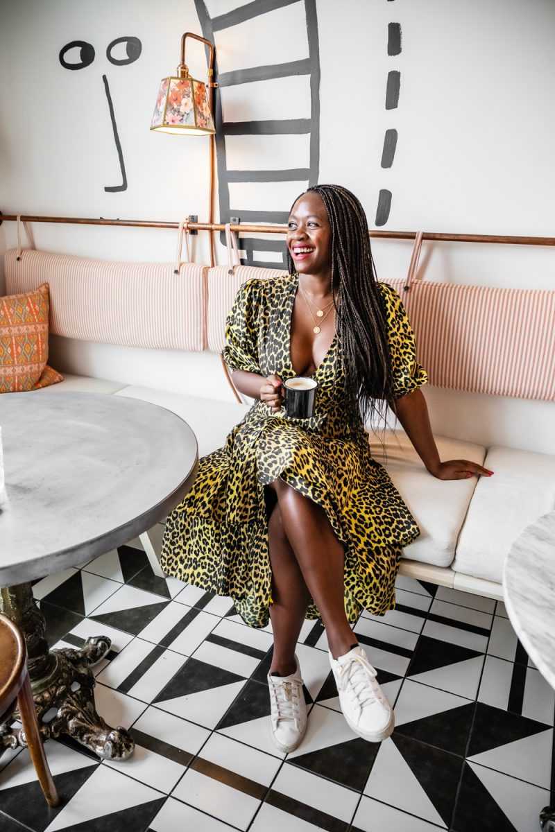 Blogging in 2020 by popular DC blogger, Alicia Tenise: image of a woman sitting in a cafe and wearing a yellow leopard print dress with white sneakers.