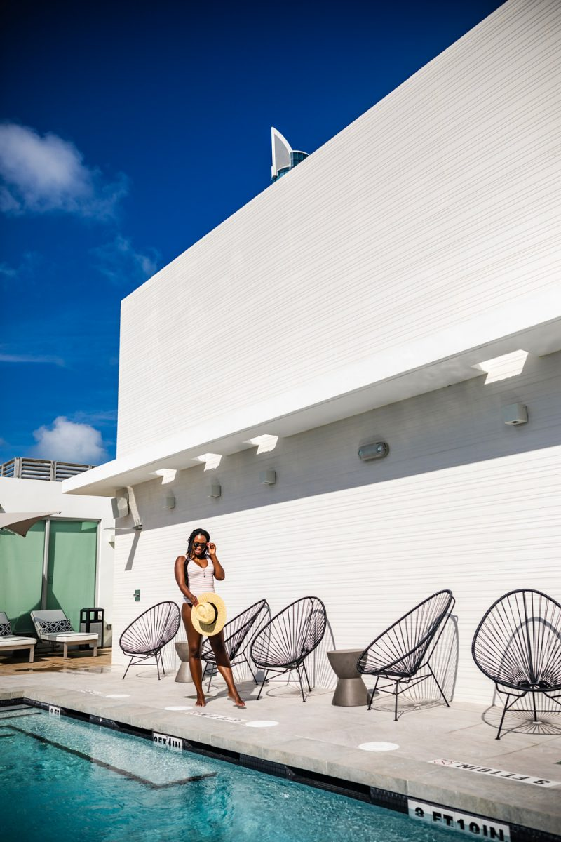 Sixty80 Design Hotel | Things to do in Miami in the Spring: image of a woman standing next to a swimming pool at Sixty80 Design Hotel.