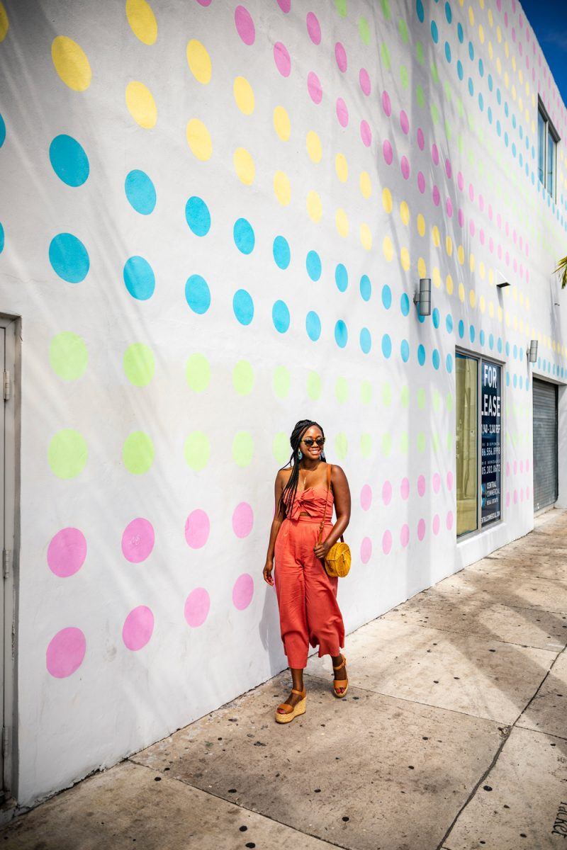 Things to do in Miami in the Spring: image of woman in front of a multicolor dot mural.