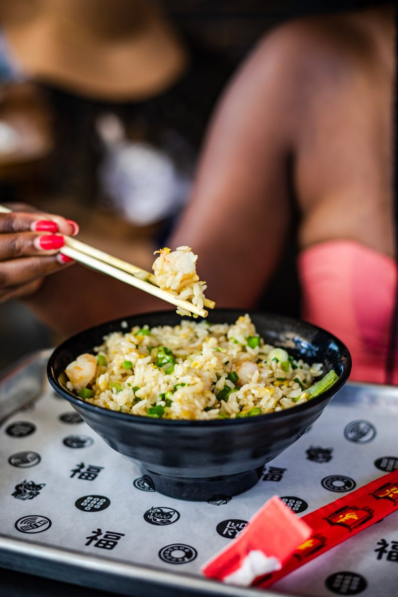 Things to do in Miami in the Spring: image of a woman eating with chop sticks.