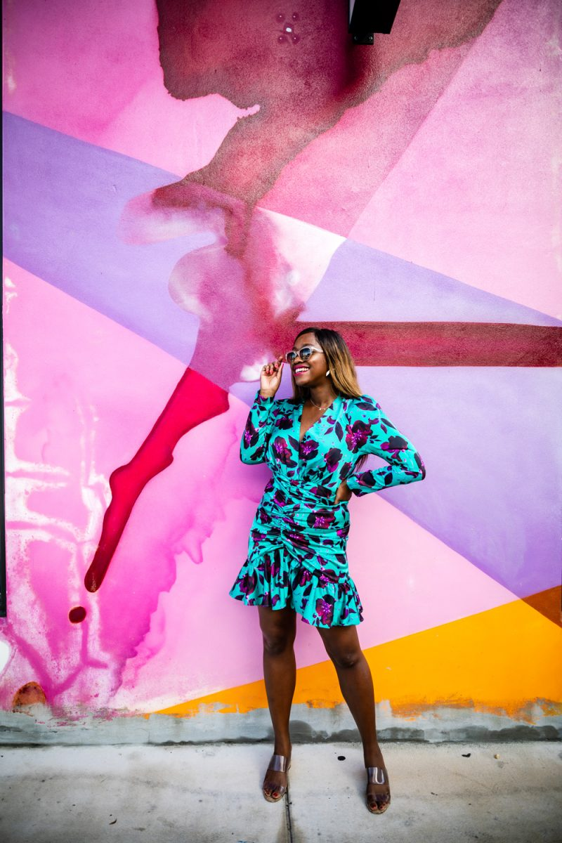 Things to do in Miami in the Spring: image of woman standing in front of a pink wall mural in Wynwood Miami.